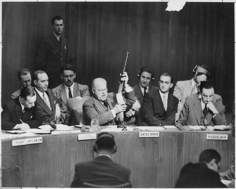At United Nations Security Council, Warren Austin, U.S. delegate, holds Russian-made sub-machine gun dated 1950, captured by American troops in July, 1950. He charges that Russia is delivering arms to North Koreans. Lake Success, New York, September 18, 1951. International News Photos. Public Domain