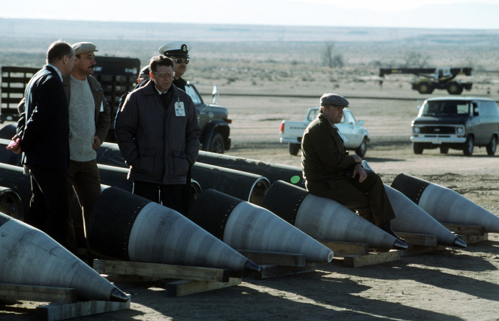 Soviet inspectors and their American escorts stand among several dismantled Pershing II missiles as they view the destruction of other missile components. The missiles are being destroyed in accordance with the Intermediate-Range Nuclear Forces (INF) Treaty, public domain