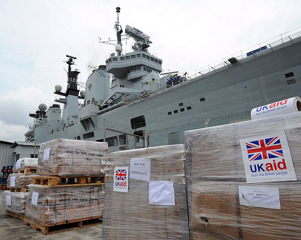 Bags of food and supplies line the dockside in Singapore as HMS Illustrious arrives to ship it to the typhoon stricken islands of the Philippines, PO(Phot) Ray Jones/MOD, Open Government Licence, v.1.0