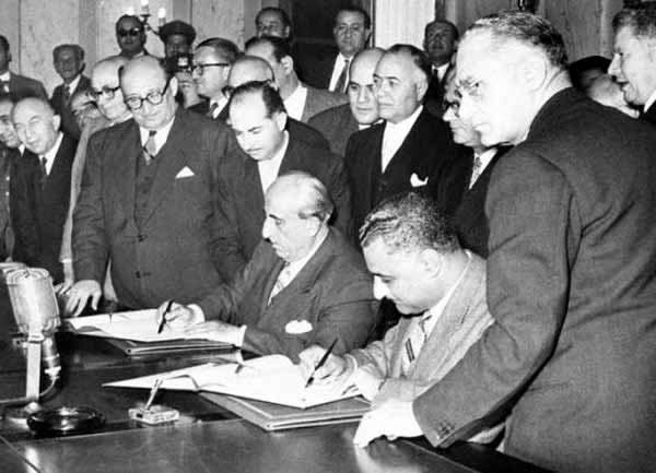 Gamal Abdel-Nasser and Shukri al-Quwatli signing the Syria-Egypt union pact. Behind Quwatli stands Abdullah al-Khani, the secretary-general of the Presidential Palace, and to his right is Prime Minister Sabri al-Asali and to al-Asali's right is Khalid al-Azm, 2 February 1958, Syrian History, public domain