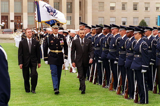 His Majesty King Mohamed VI of Morocco (right) inspects the joint service honor guard at the Pentagon during a full honor arrival ceremony hosted by Secretary of Defense William S. Cohen (left) on June 21, 2000. Escorting the two dignitaries is Col. Thomas M. Jordan, U.S. Army, commander of the 3rd U.S. Infantry (The Old Guard)., 21 June 2000, US State Department, Public domain
